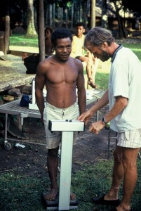 Een man op Kitava wordt gewogen